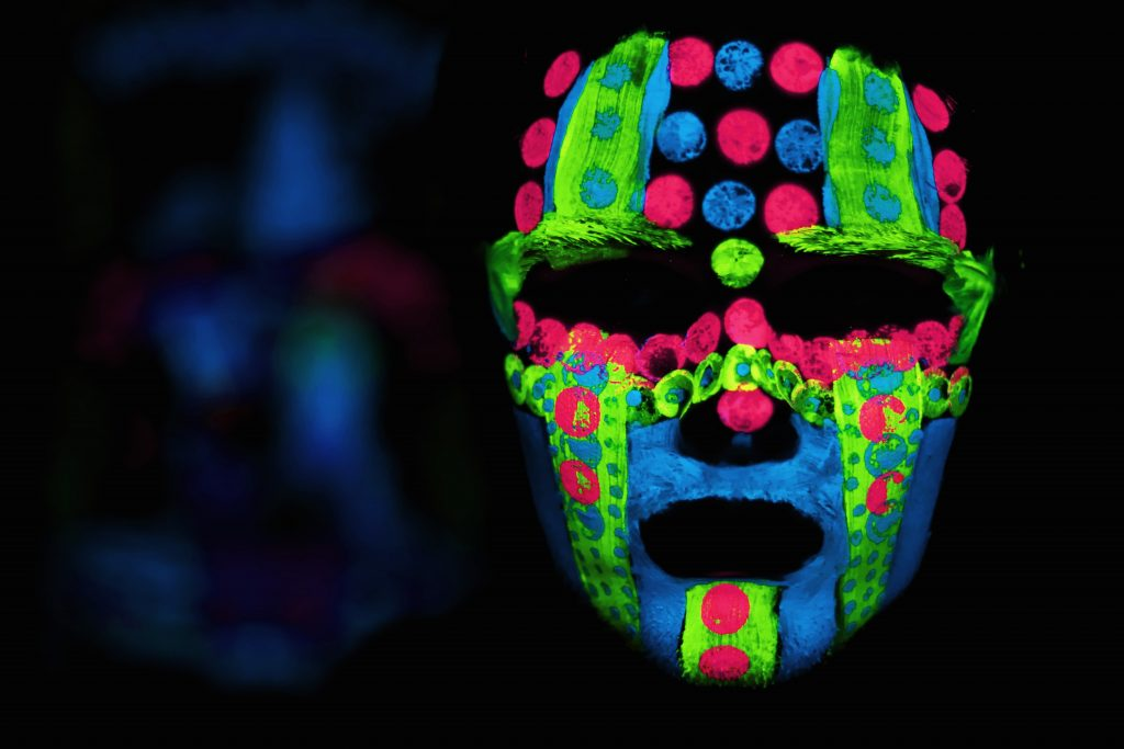 black figure wearing multi-colored irridescent face mask