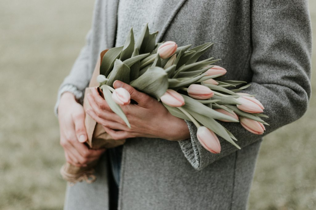 how to let go and move on - woman grey coat pink tulips