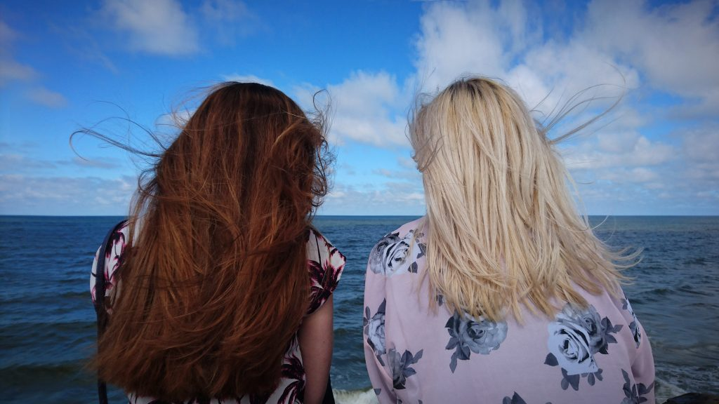 women friends talking by the ocean - decision making